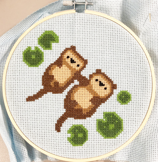 Photo of a cross stitch of 2 sea otters holding hands in the water, with lily pads around them.